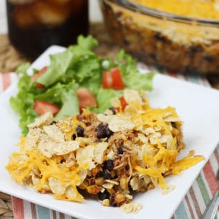Mexican cicken casserole on a white plate with a side salad behind it