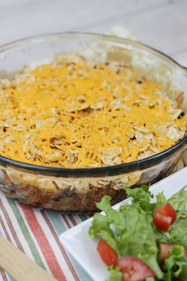 Finished casserole in a glass baking dish next to a side salad