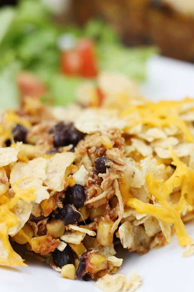 A close up picture of Mexican Chicken Casserole on a white plate with a salad in the background