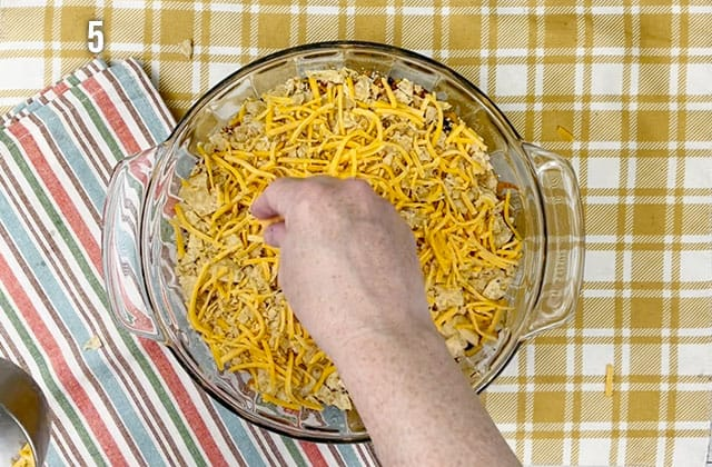 Sprinkling cheese over the top of the casserole