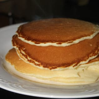 Homemade pancakes stacked on a white plate
