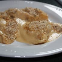Pierogies au gratin cooked and served on a white plate