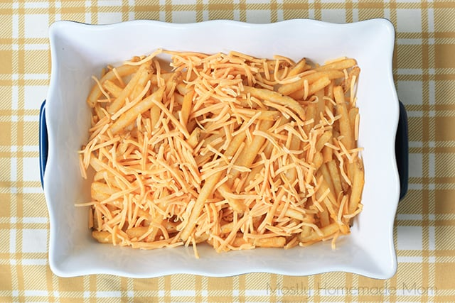 french fries in a baking dish with shredded cheddar cheese