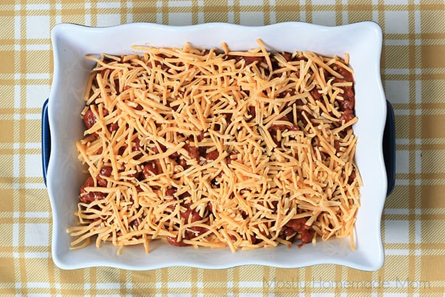 baked french fries in a baking dish topped with cheese and chili