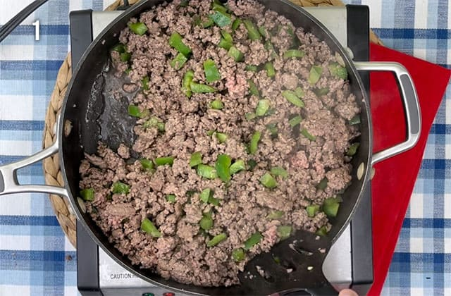 Cooking ground beef and green peppers in a deep skillet
