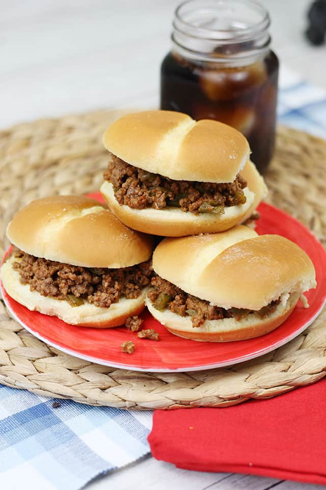 Slow cooker sloppy joes stacked on a red plate with a glass of soda