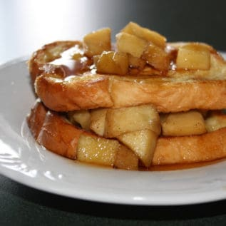 A serving of apple stuffed french toast on a white plate topped with syrup