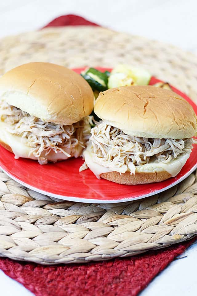 Two shredded chicken sandwiches on a red plate