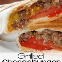 A grilled cheeseburger wrap sliced in half and sitting on a white plate