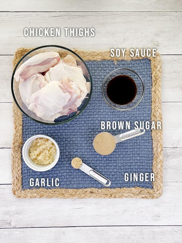 Ingredients for slow cooker sticky chicken on a blue placemat