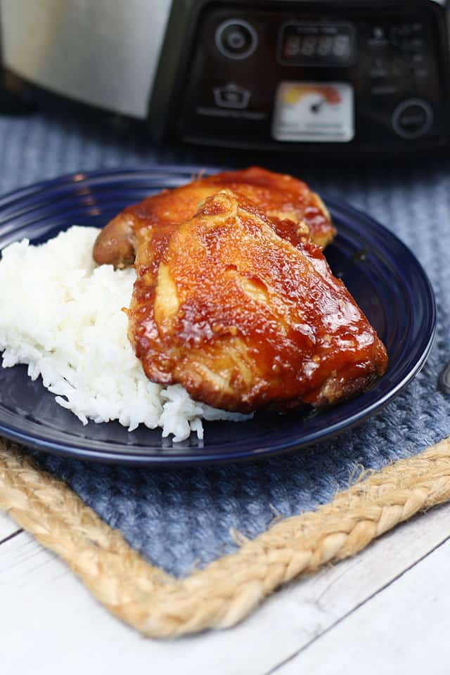 Slow cooker sticky chicken pieces on top of rice on a blue plate