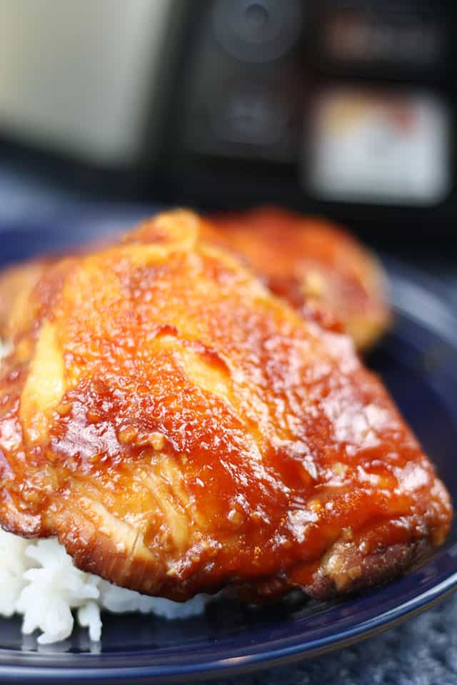 Easy slow cooker sticky chicken on a blue plate next to cooked rice