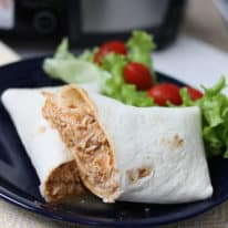 Slow cooker salsa chicken wraps on a blue plate with a side salad next to it