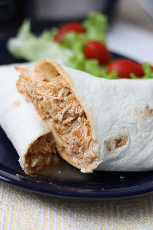A tortilla wrap filled with cooked chicken, sliced in half, on a blue plate