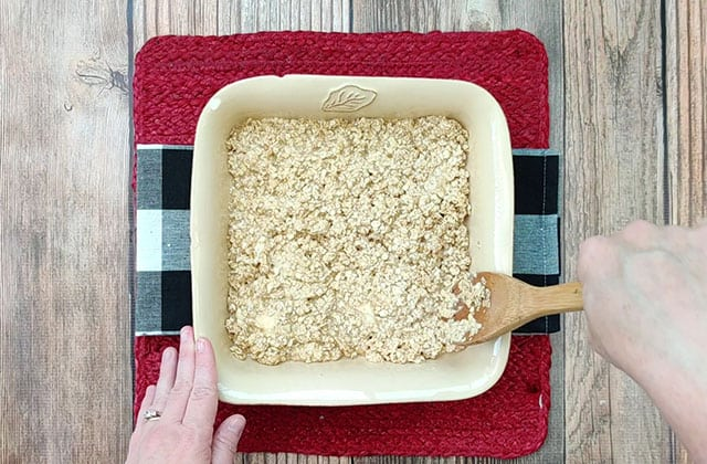 Spreading oatmeal mixture into a baking dish.