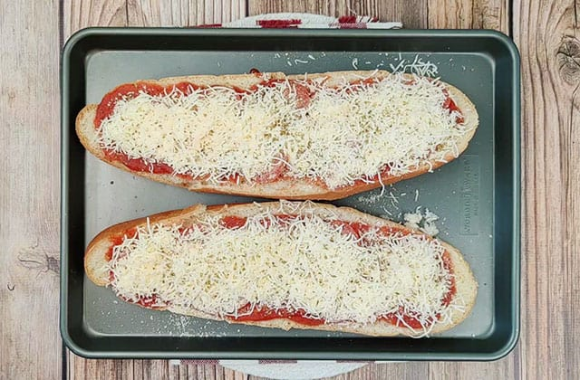 French bread pizza on a baking sheet ready to be baked in the oven