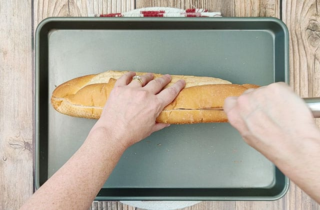 Cutting a loaf of French bread in half on a baking sheet