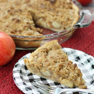 A slice of apple crumb pie in front of the whole pie with some apples
