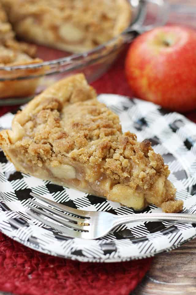 A slice of apple crumb pie on a black plaid paper plate