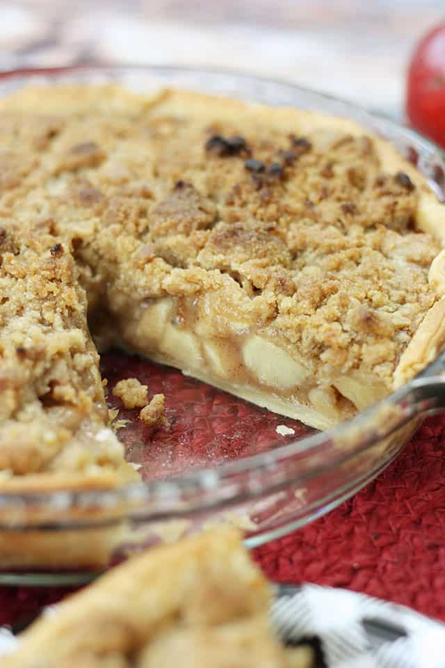 An apple crumb pie in a glass pie plate with a slice taken out
