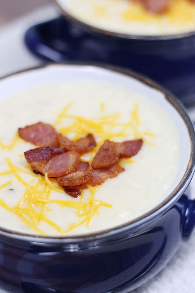 A close up of crockpot baked potato soup topped with bacon and cheese
