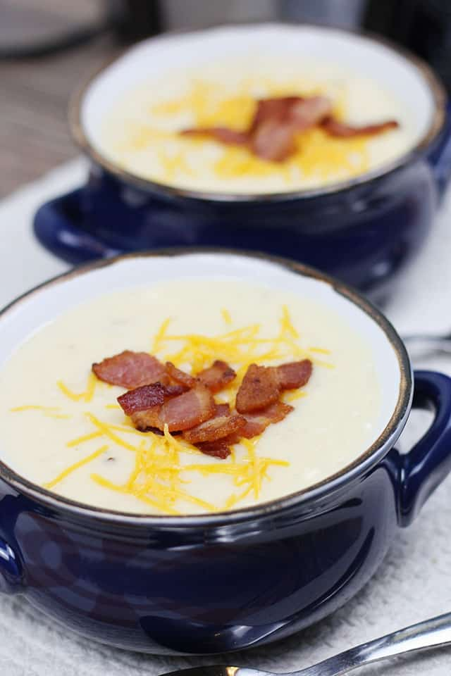 Two bowls of crockpot baked potato soup with bacon and cheese