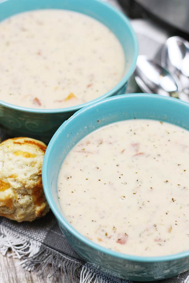 Two bowl of tomato basil parmesan soup with spoons and biscuits