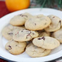 Cranberry orange cookies on a white plate with an orange in the background