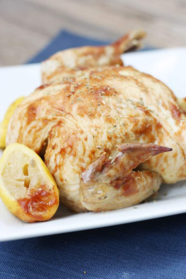 Crockpot BBQ rotisserie chicken on a serving plate next to a lemon