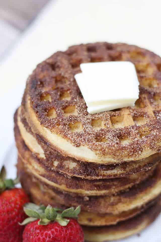 A stack of churro waffles topped with butter