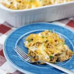 Ranch chicken enchilada casserole on a blue plate with a fork