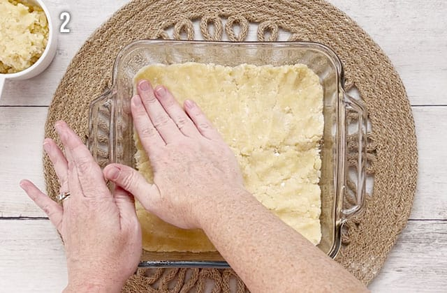 Pressing sugar cookie dough into a glass baking dish to make a crust