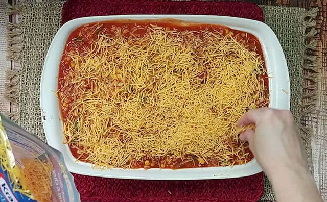 Stuffed pepper casserole being topped with shredded cheese before baking