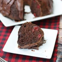 A slice of cherry chocolate cake on a white plate with the whole cake in the background