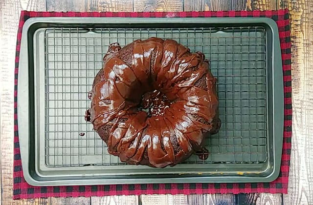 A chocolate cherry cake on a wire rack with frosting drizzled on top