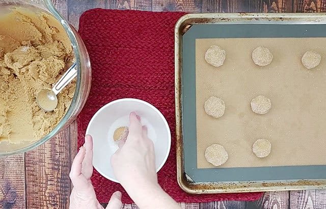Rolling ginger snap cookies in sanding sugar before placing on cookie sheets