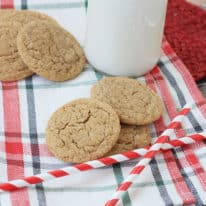 Ginger snaps cookies on a plaid napkin with milk in the background