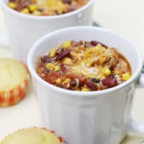 Two white soup mugs filled with crockpot chicken chili with cornbread muffins next to them
