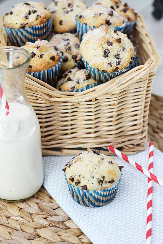 Chocolate chip muffins in a basket next to a glass of milk with a straw