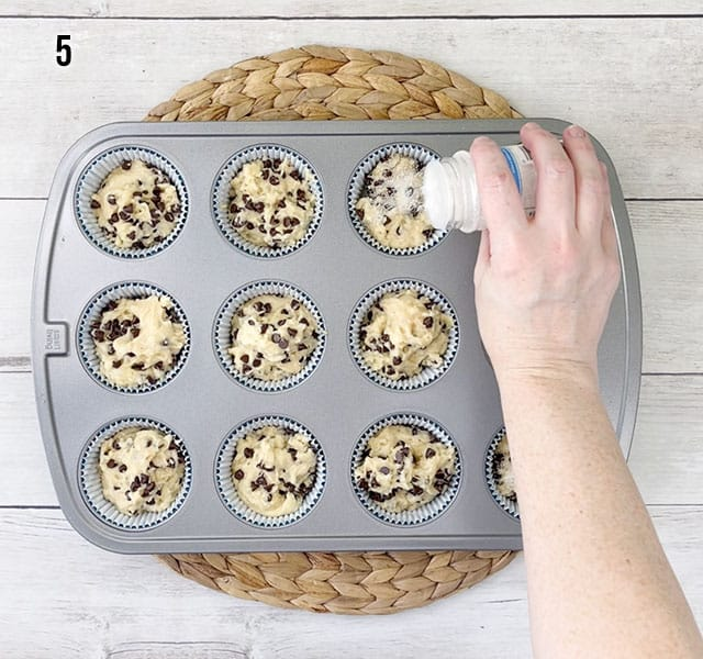 Sprinkling sanding sugar over muffin tops in a muffin tin before baking