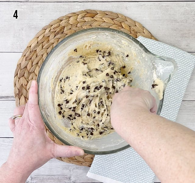 Stirring wet ingredients with dry ingredients in a glass bowl for muffins