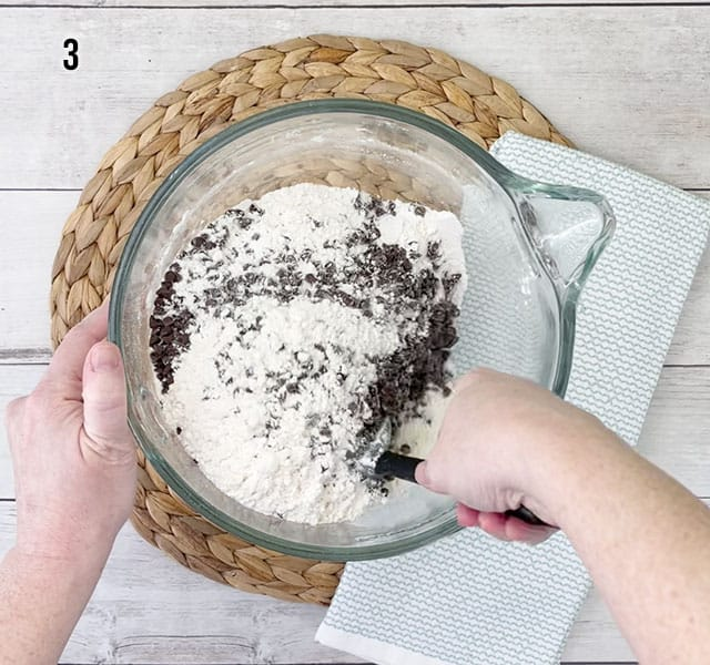 Stirring in miniature chocolate chips to the flour mixture in a glass bowl