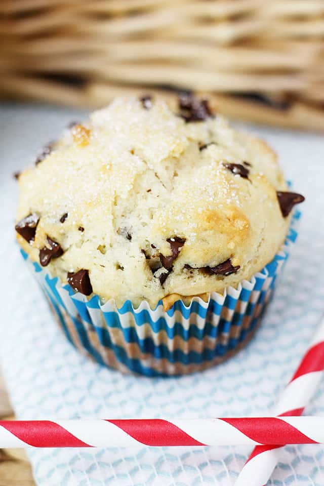 A chocolate chip muffin with blue striped liner next to a red straw