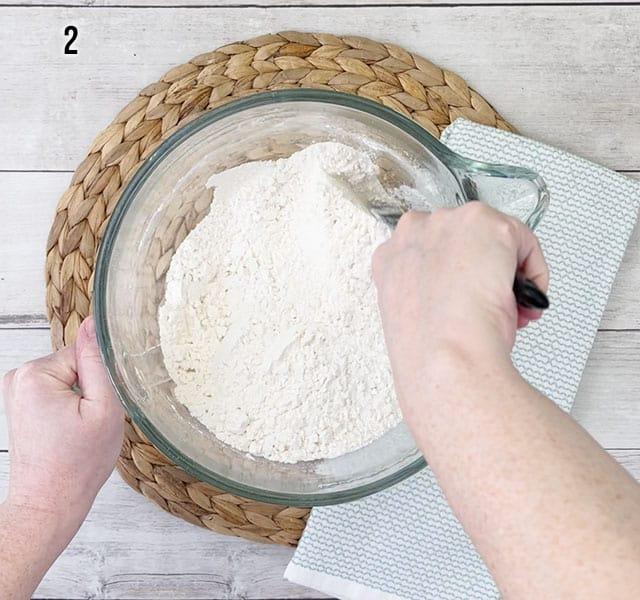 Stirring flour, sugar, baking powder, and salt in a glass mixing bowl