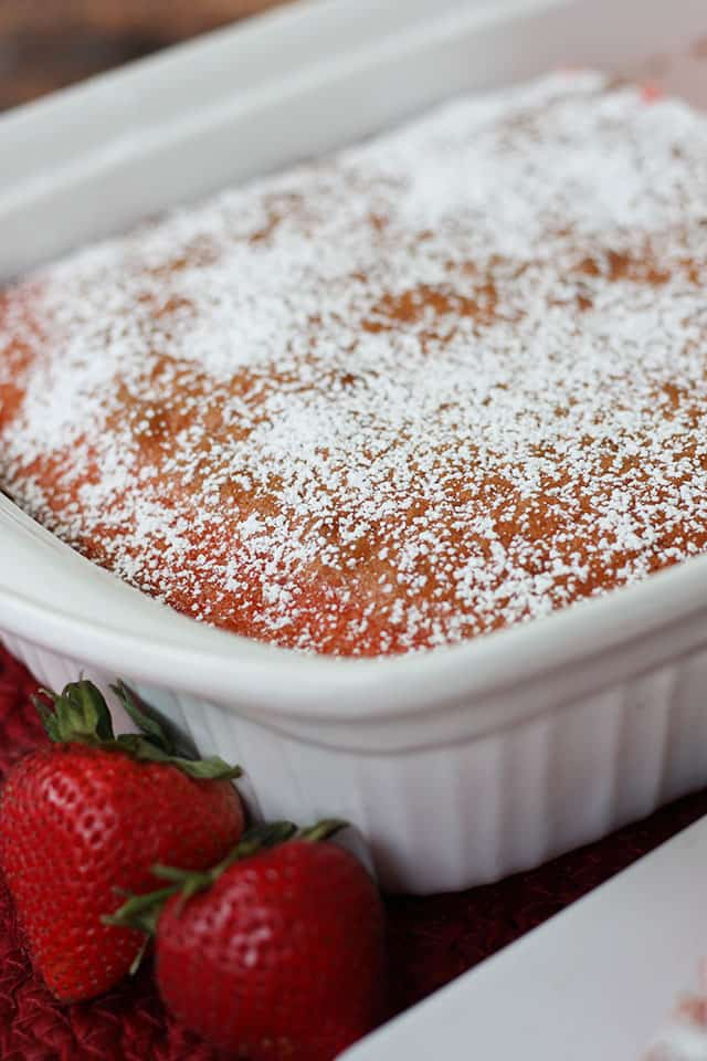 Strawberry cake in a white baking dish topped with powdered sugar