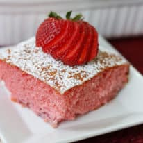 Strawberry jello cake on a white square plate topped with powdered sugar and sliced strawberry