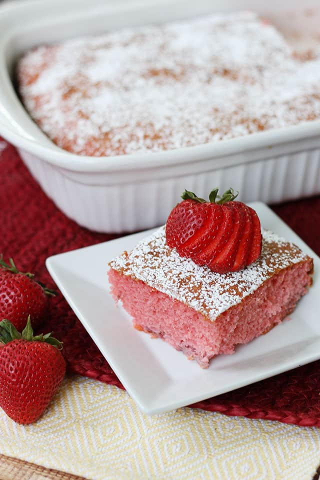A piece of strawberry jello cake on a white plate with the cake pan in the background