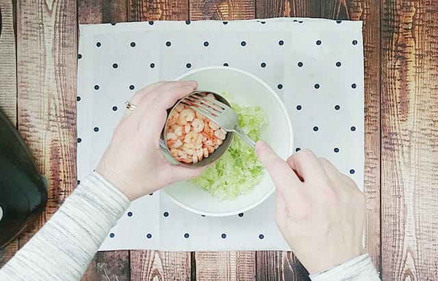 Adding tiny shrimp to a bowl with celery, onion, and cream cheese
