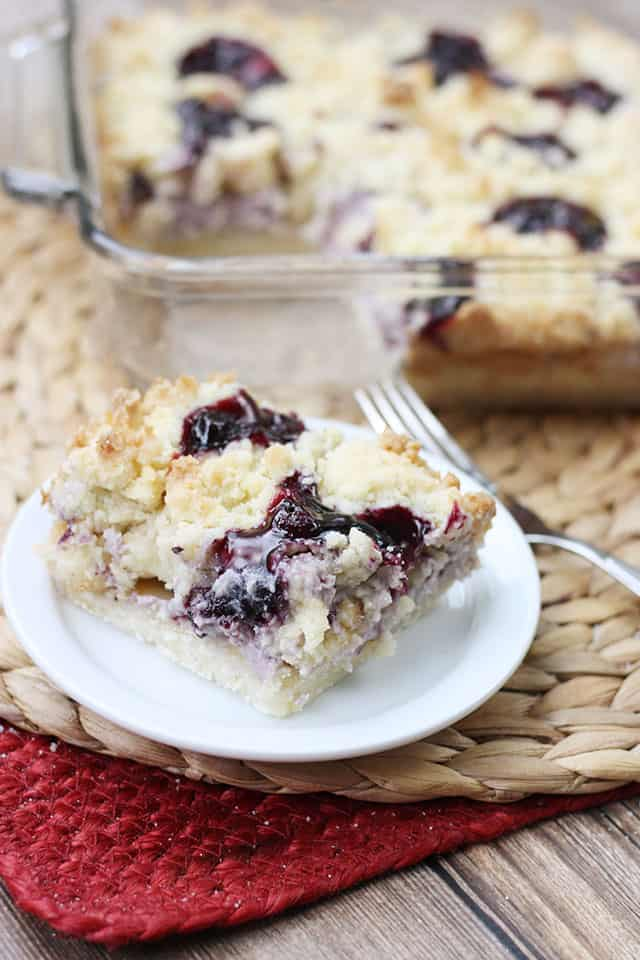 A slice of blueberry cobbler sugar cookie squares on a white plate