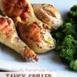 Grilled chicken drumsticks on a white plate next to steamed broccoli